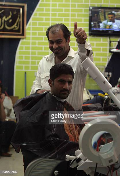 A barber gestures from his shop as he cuts a customer's hair on January 29 2009 in Basra Iraq Many areas in Iraq are preparing for provincial...