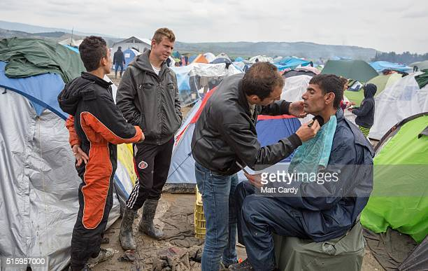 A barber gives a man a shave at the Idomeni refugee camp on the Greek Macedonia border on March 16 2016 in Idomeni Greece The decision by Macedonia...