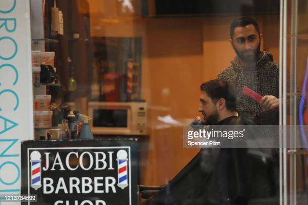 A barber gives one of his last haircuts before being forced to close on March 20 2020 in New York City Schools businesses and most places where...
