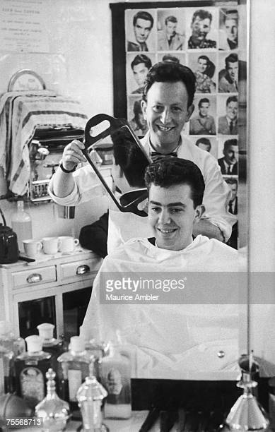 A barber holds a mirror up for a customer to check his new hairstyle at Angel Rose's barber's shop in Tottenham Court Road London 13th November 1954...