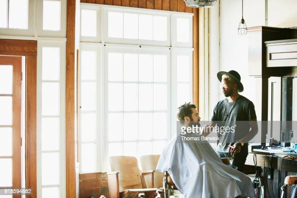 barber in discussion with client before hair cut in barber shop - 美容室 椅子 ストックフォトと画像