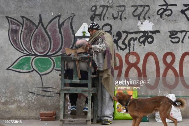 Barber is seen at work on a cold morning, on December 29, 2019 in New Delhi, India. Severe cold wave conditions continue in northern India. It was...