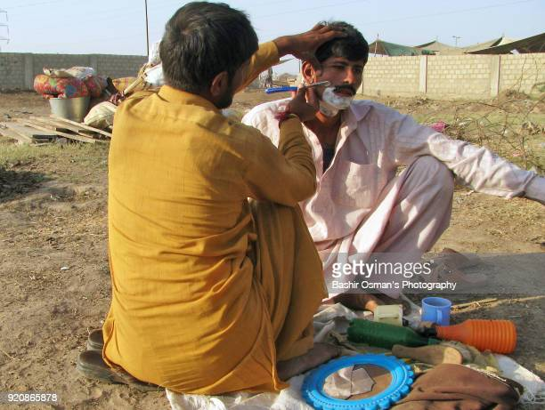 a barber is shaving face of man - pakistani culture stock photos and pictures