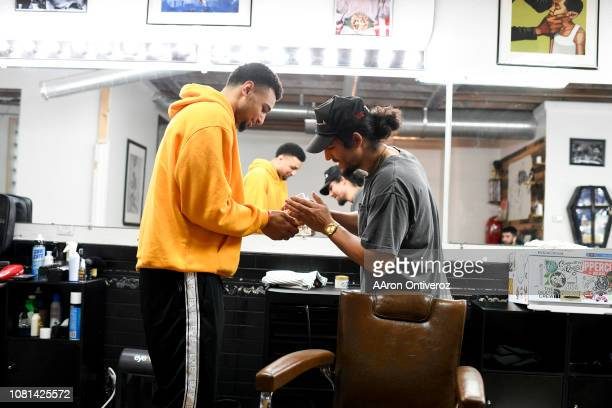 Barber Josue 'Sway' Navarro shares a handful of gummy bears with Denver Nuggets guard Jamal Murray after giving him a fresh cut at Bellwether...