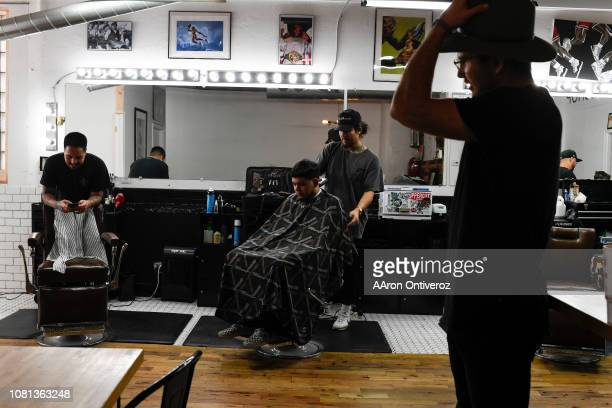 Barber Josue 'Sway' Navarro works on Gerardo Arredondo as fellow barber Gabriel Maestas jokes with customer Elijah DeFrees at Bellwether Barbershop...
