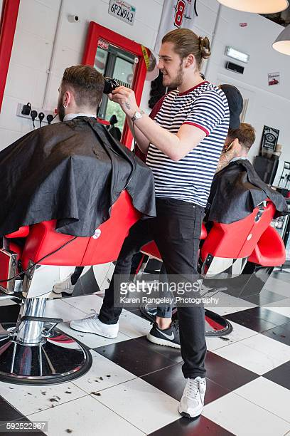 Barber Nathanael chats to client Alex while he styles his hair in cutting edge barbershop in Leeds
