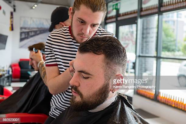 Barber Nathaneal concentrates as he carefully trims client Zach's sidies