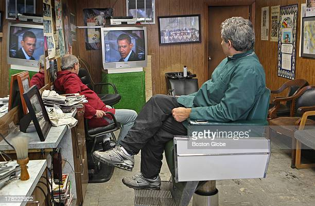Barber Ottavio LoGrasso sits in a barber chair at his store on West Broadway in South Boston watching President Barack Obama's inauguration on the...