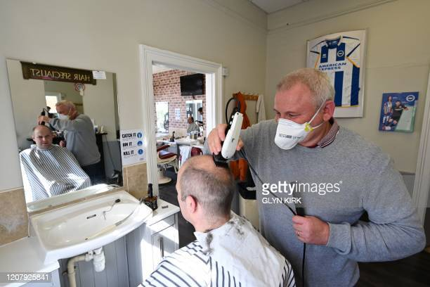 Barber Paul Harris wears a protective face mask as he cuts the hair of a customer in Brighton on the south coast of England on March 21 a day after...