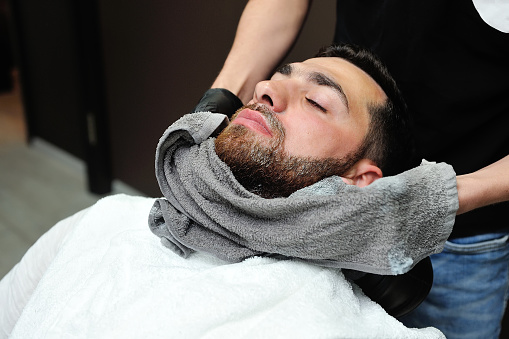 Barber preparing man face for shaving with hot towel 869786676