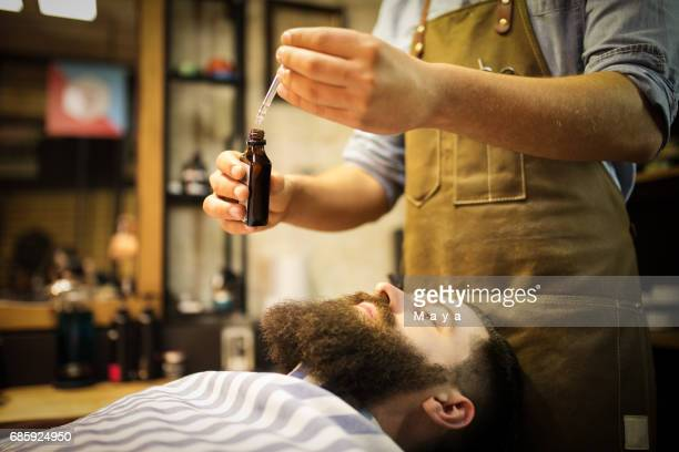 Barber putting beard oil to client