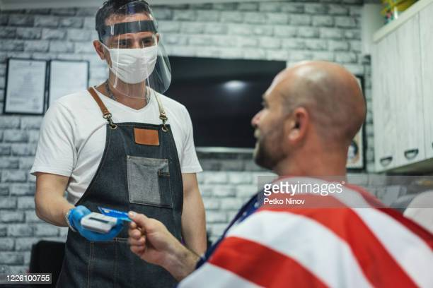 barber receiving cashless payments during coronavirus pandemic - reopening stock pictures, royalty-free photos & images