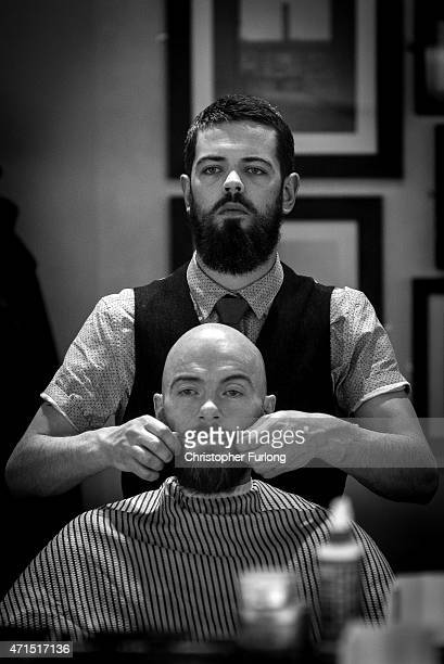 Barber Ricky Trim waxes a customer's moustache in Manchester's Barber Barber a 'gentleman's saloon' style male barber shop on April 29 2015 in...
