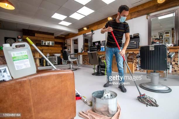 Barber Scott Camilleri mops the floor as he prepares to reopen Northern Souls barbershop in Marple on Saturday on June 30 2020 in Stockport England...