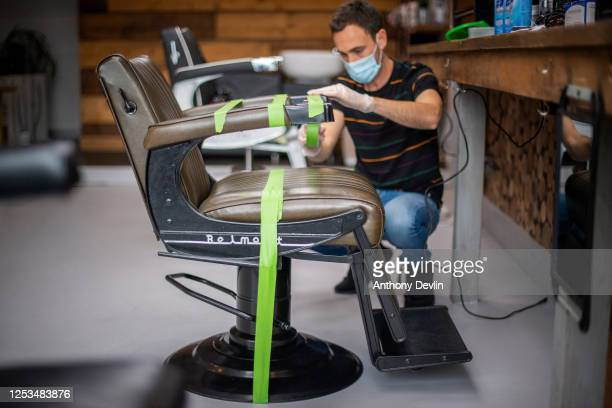 Barber Scott Camilleri tapesoff a chair to observe the two meter rule as he prepares to reopen Northern Souls barbershop in Marple on Saturday on...