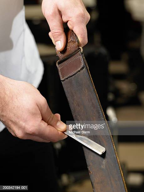 Barber sharpening razor blade on leather strip, close-up of hands
