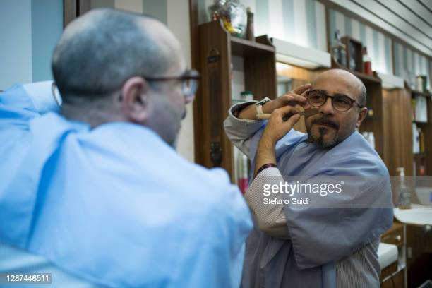 A barber shaves his beard inside his barber shop in Via Barbaroux on November 24 2020 in Turin Italy Via Barbaroux is an old area in Turin which has...