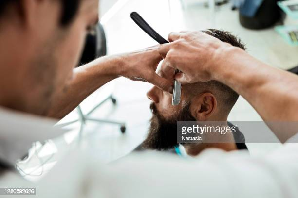 barber shaves the beard of the client - shaved stock pictures, royalty-free photos & images