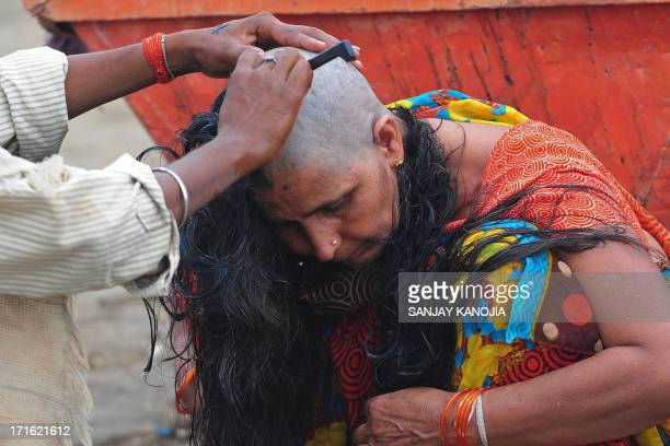 A barber shaves the head of a female devotees as part of a ritual where believers donate their hair at the Sangam in Allahabad on June 27 2013...