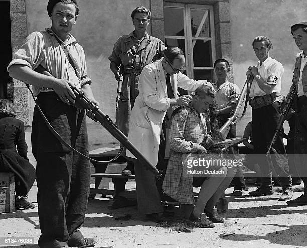 A barber shaves the head of a woman accused of being a Nazi collaborator surrounded by members of the Free French Resistance with rifles | Location...