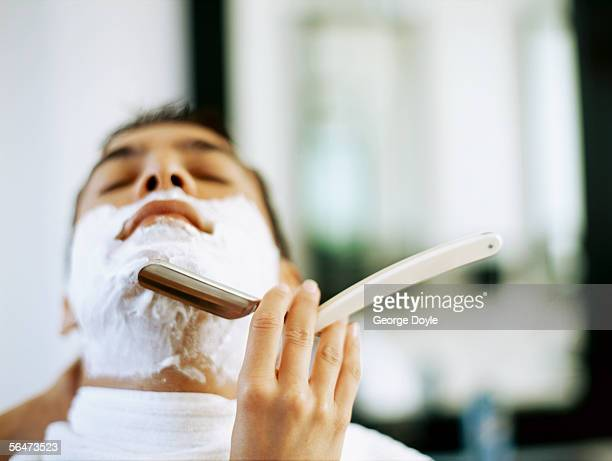 barber shaving a young man