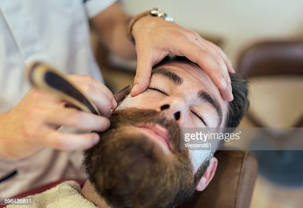 Barber shaving beard of a customer