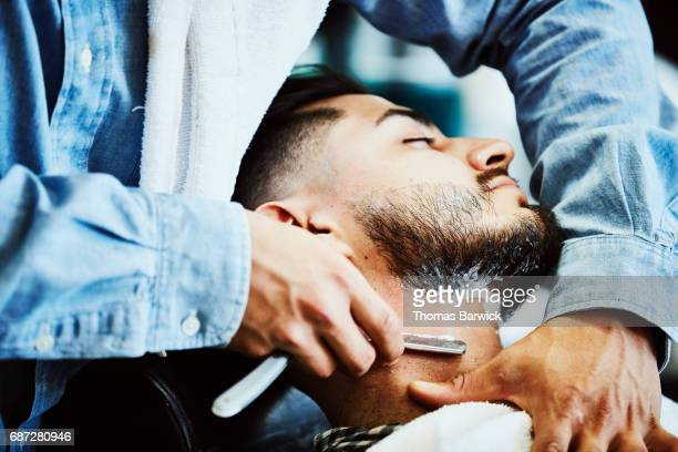 Barber shaving client with straight razor