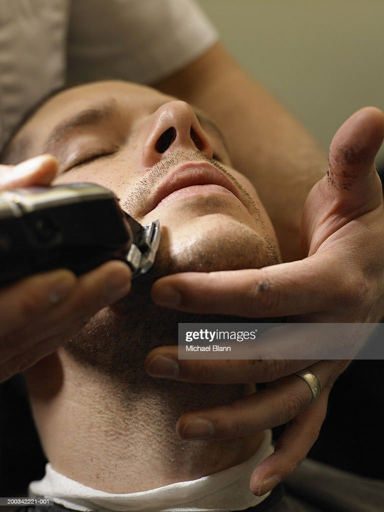 Barber shaving man, close-up : Stock Photo