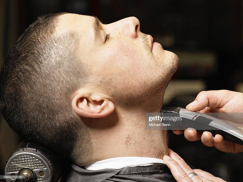 Barber shaving man, close-up, profile : Stock Photo