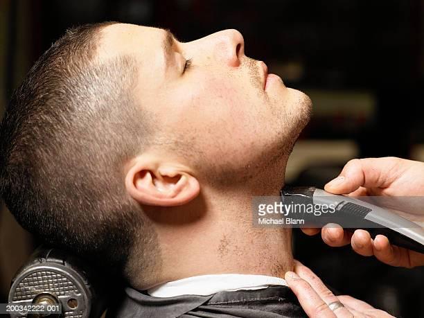 Barber shaving man, close-up, profile