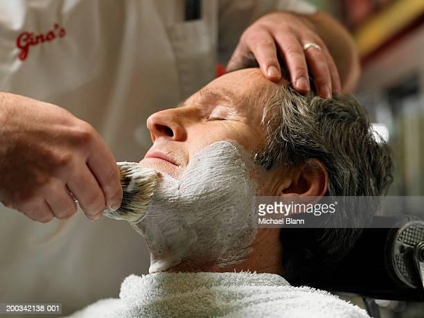 Barber shaving senior man, close-up