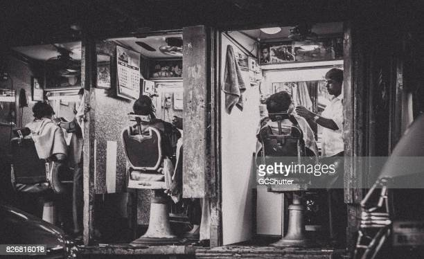 barber shop tending to its customers. - barber shop stock photos and pictures