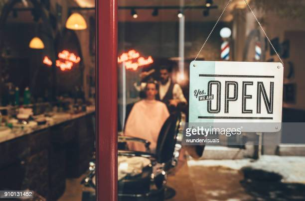 Barber shop window with open sign and barber working indoors