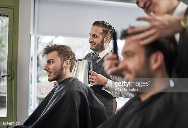 Barber showing client his haircut