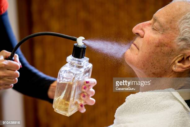 Barber Spraying Aftershave on Senior Man