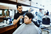 barber spraying water while combing out