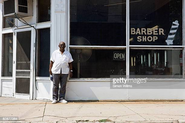 Barber standing in front of his barber shop