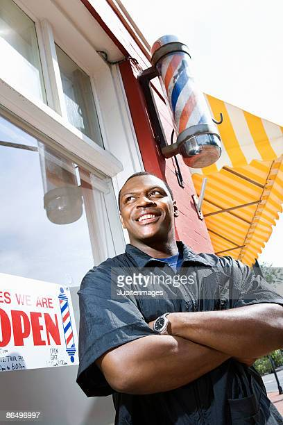 barber standing proud outside barbershop - barber pole stock photos and pictures