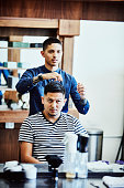 barber styling clients hair after hair