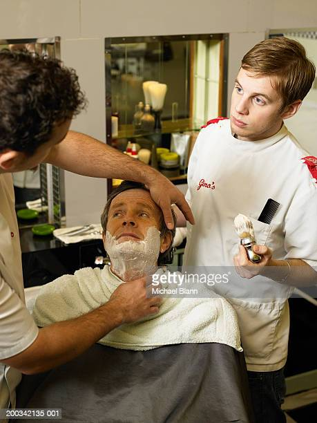 Barber teaching colleague to shave man