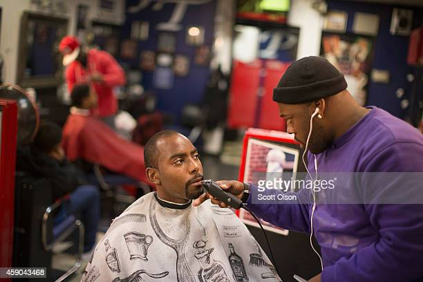 Barber Tony Henley trim a customer's beard at the Prime Time Barber and Beauty shop on West Florissant Street November 15 2014 in Ferguson Missouri...