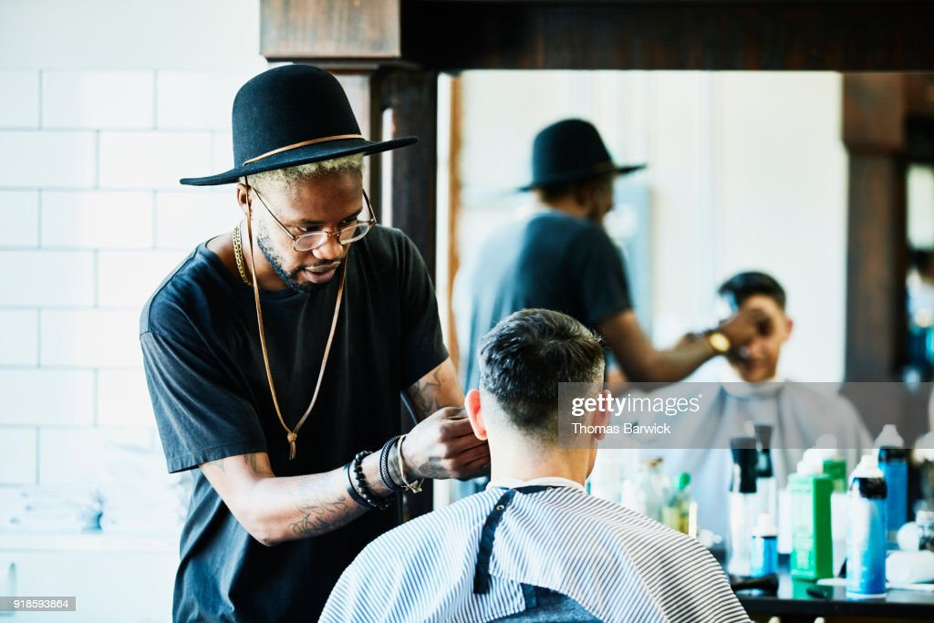 Barber trimming clients bangs during hair cut in barber shop : Stock Photo