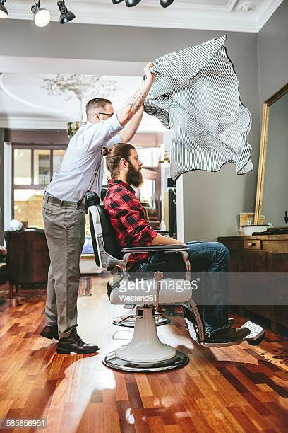 Barber tying cape around customer