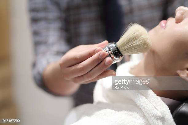 barber using shaving brush in barber shop - shaving brush stock photos and pictures