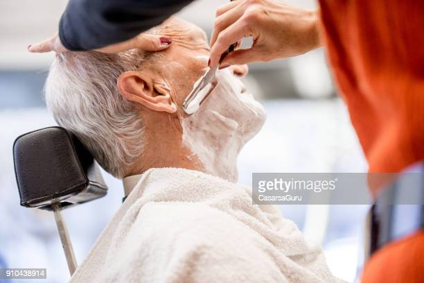 barber using straight razor to shave senior man - shaving brush stock photos and pictures