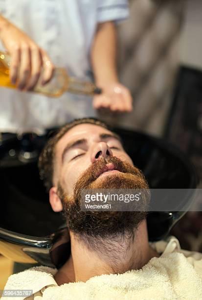 Barber washing hair of a customer