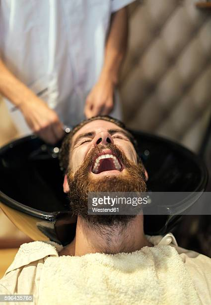 Barber washing hair of a customer with open mouth