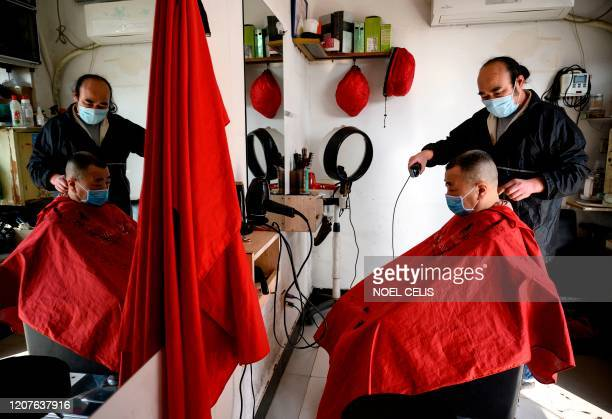 TOPSHOT A barber wearing a face mask applies the finishing touches on the hair of a customer in Jiujiang a city which sits on the border between...