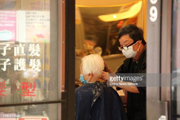 A barber wearing a protective mask cuts a customer's hair at a barber shop at Chinatown on May 28 2020 in Vancouver Canada The Coronavirus pandemic...