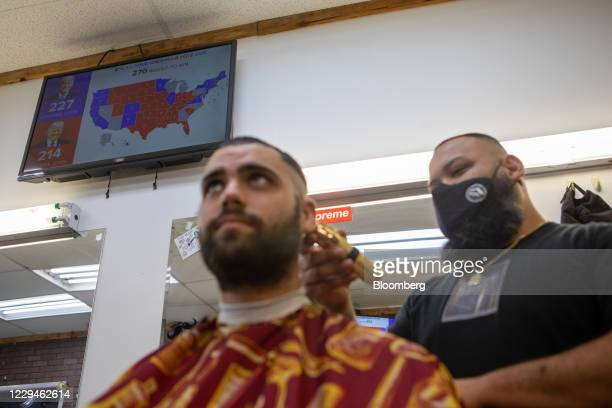Barber wearing a protective mask cuts a customer's hair in front of a television showing the news during the 2020 Presidential election in Miami,...